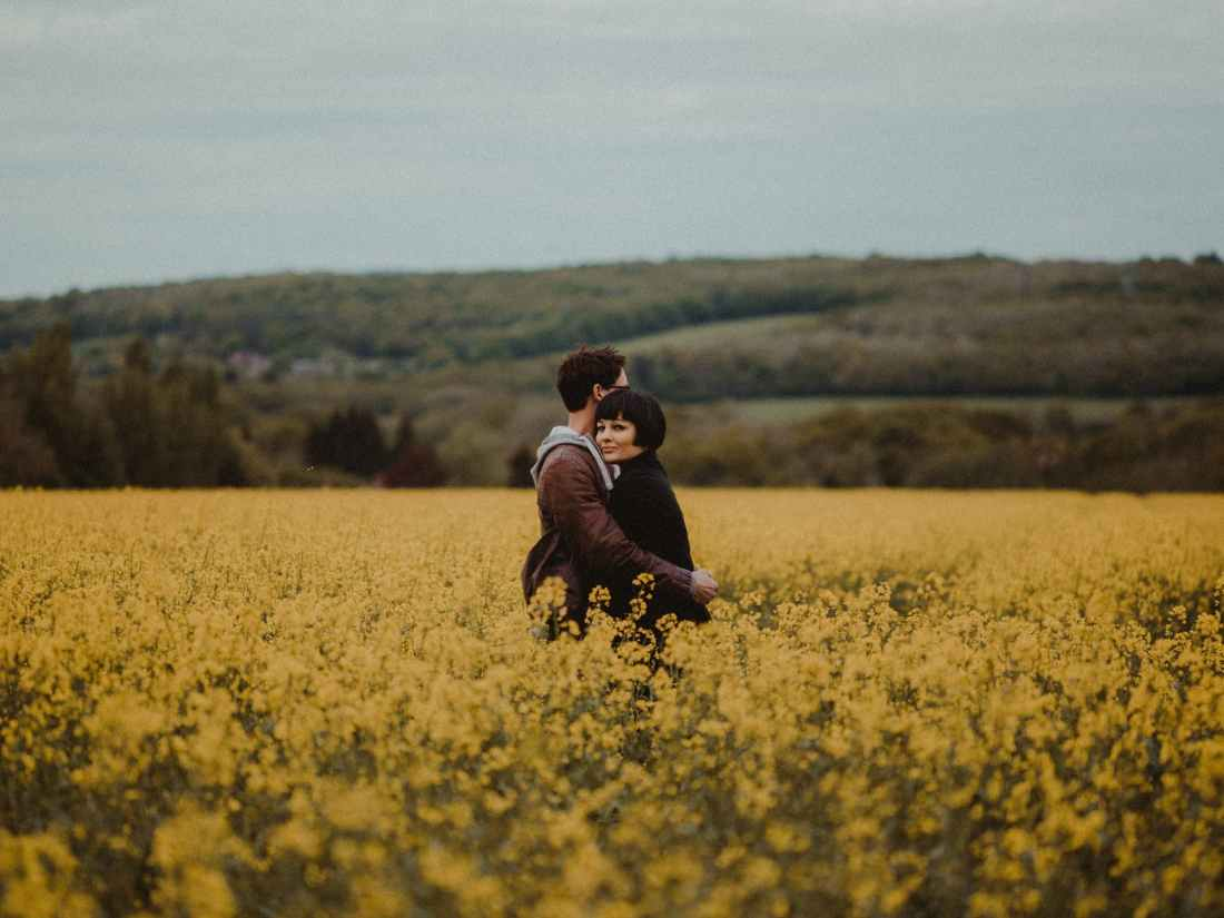 couple hugging in the middle of flower field