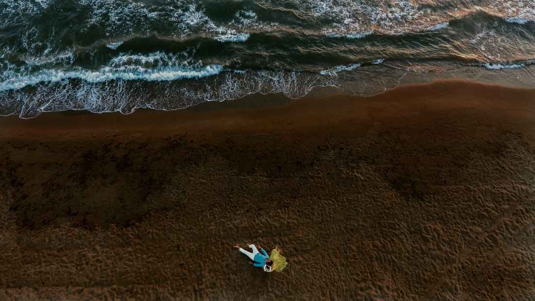 aerial photo of couple lying on seashore